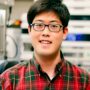 Matthew, wearing a red and green plaid shirt and black glasses, standing in a lab