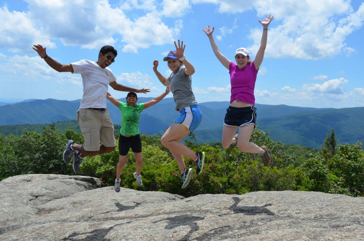 Four individuals jump in the air on an exposed rock surface.