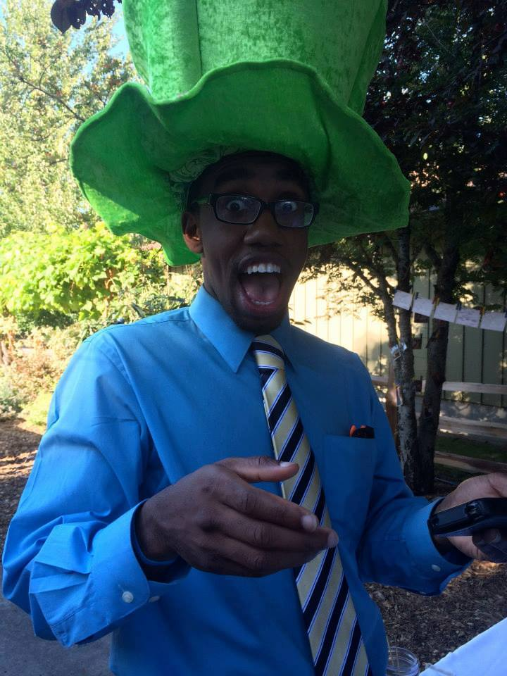 A man wears a large green hat and an expression of surprise