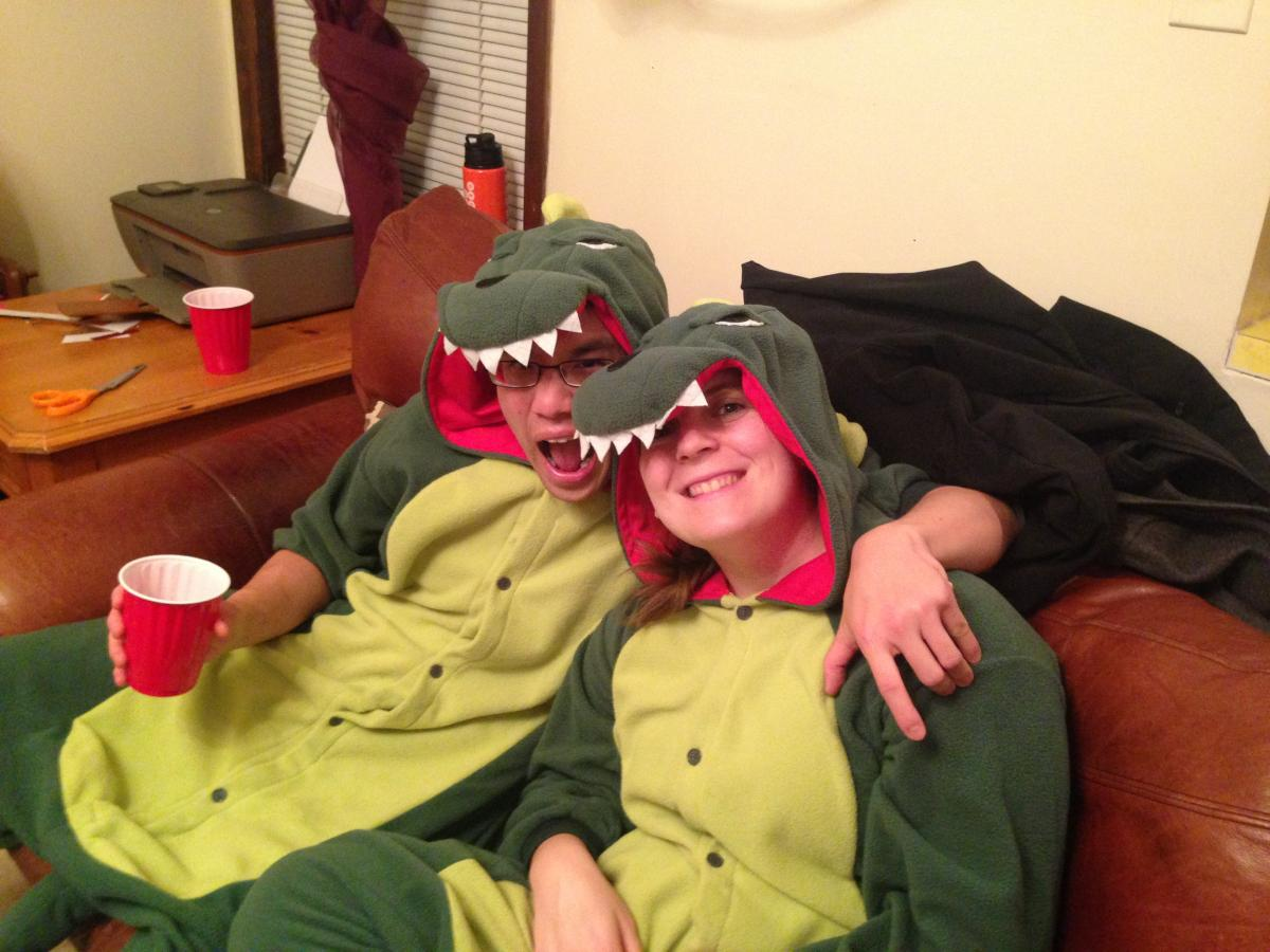 Two individuals wearing matching alligator costumes relax on a couch