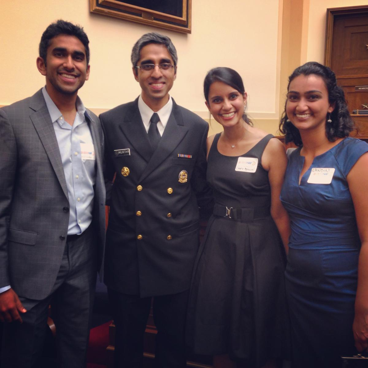 Three students stand side by side with the Surgeon General of the U.S.