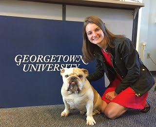 "CC Borzilleri with Jack the bulldog in front of desk that has ""Georgetown University"" text"