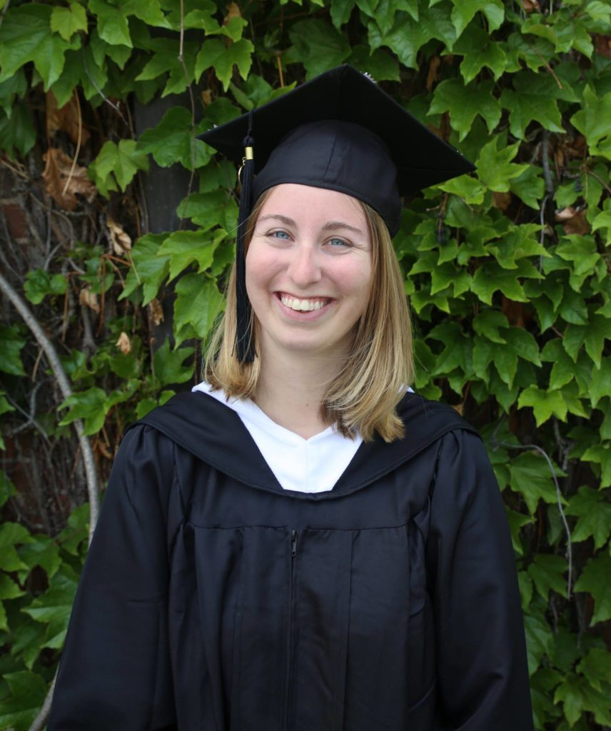 Katie O'Hara in cap and gown in front of ivy background