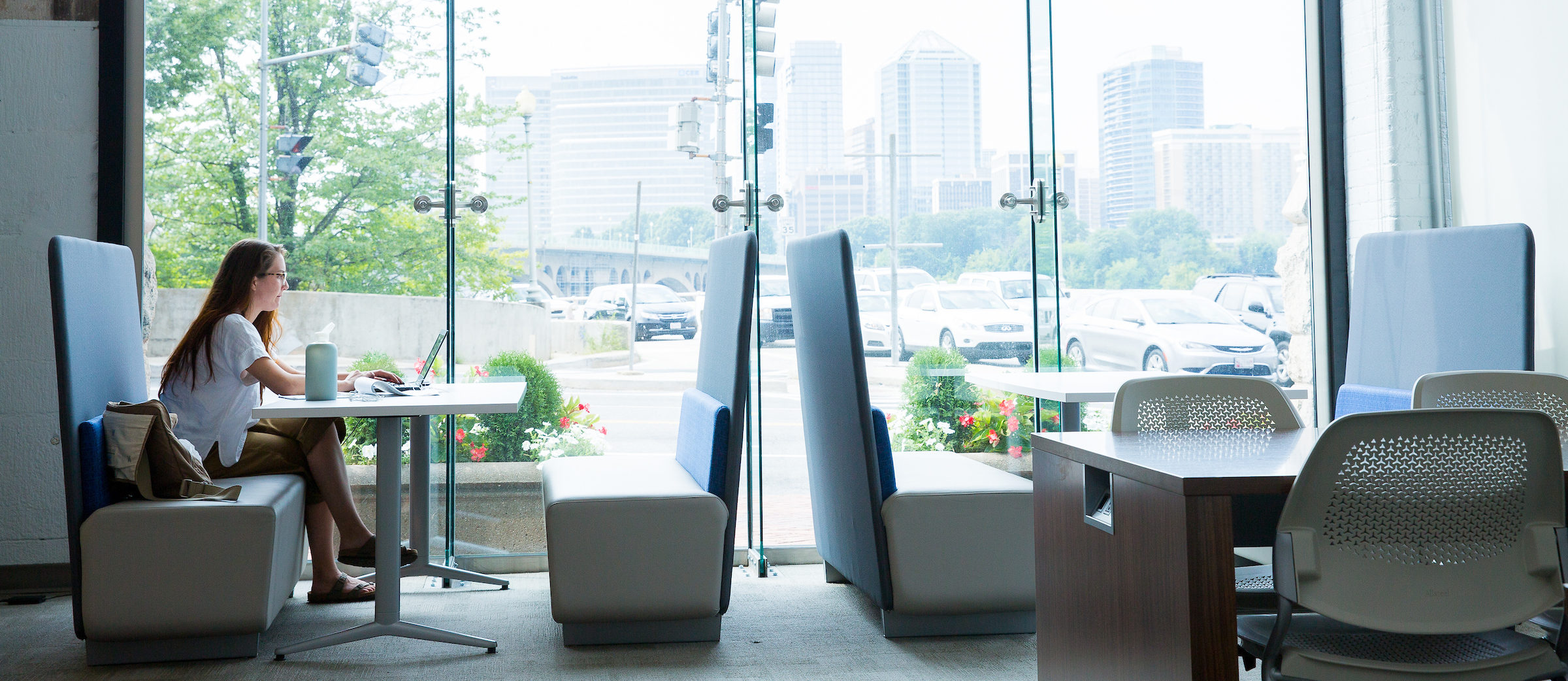 a student sits in a booth near the window in the graduate study lounge in Car Barn